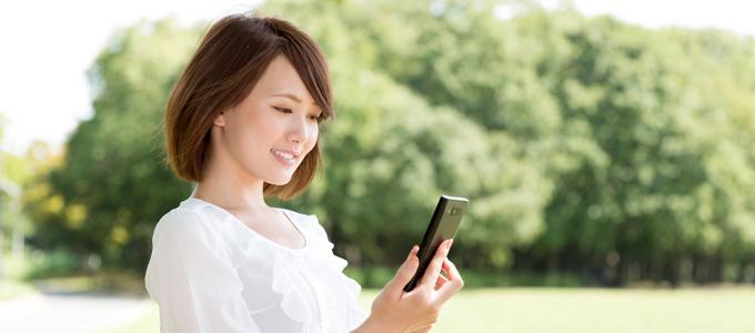 外で女性が携帯を操作